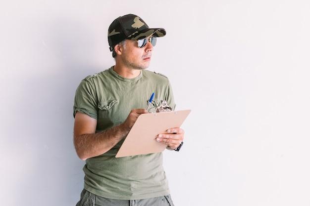 Militaire man met camouflagepet en zonnebril, schrijvend in een rapport in een map, op een witte muur