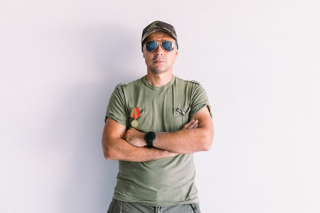 Militaire man met camouflagepet en zonnebril, versierd, met gekruiste armen, op een witte muur