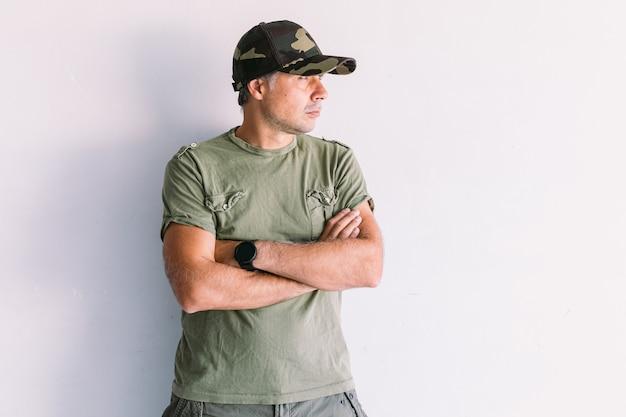 Militaire man met camouflagepet, gekruiste armen, op een witte muur