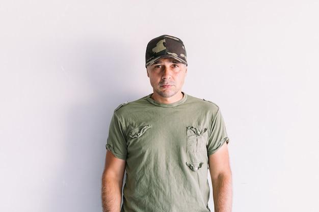 Militaire man met camouflagepet op een witte muur