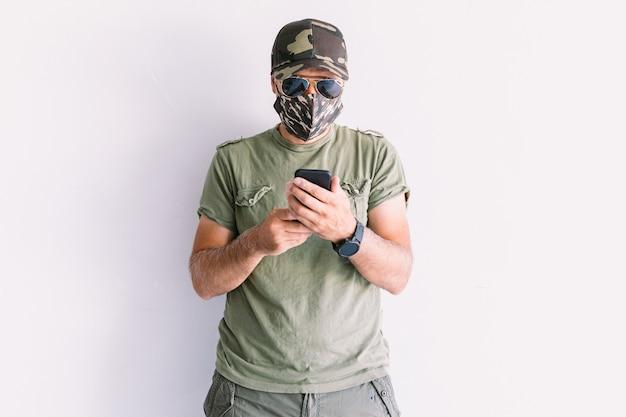 Militaire man met camouflagepet, zonnebril en camouflagemasker, kijkend naar zijn smartphone, op een witte muur