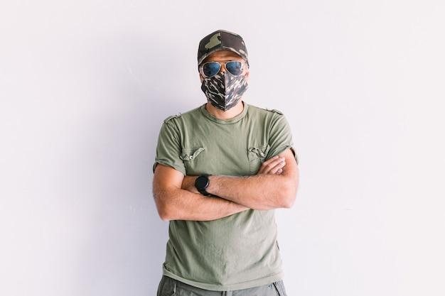 Militaire man met camouflagepet, zonnebril en camouflagemasker, met gekruiste armen, op een witte muur