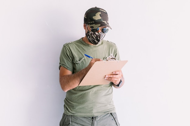 Militaire man met camouflagepet, zonnebril en camouflagemasker, schrijft een rapport in een map, op een witte muur
