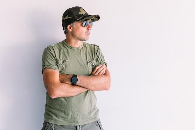 Militaire man met zonnebril en camouflage pet, armen gekruist, op een witte muur