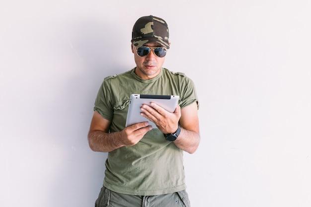 Militaire man met zonnebril met een tablet op een witte muur