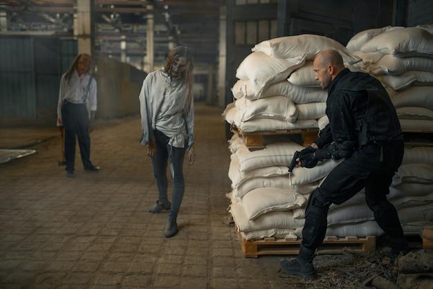 Militaire man verbergt zich voor zombies in verlaten fabriek. horror in de stad, griezelige beestjes, doomsday apocalyps, bloedige kwaadaardige monsters