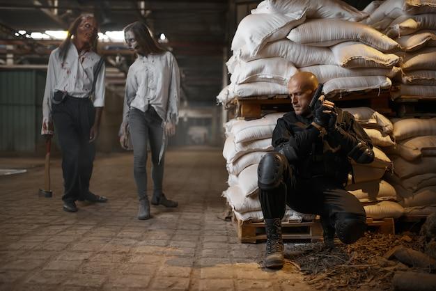 Militaire man verbergt zich voor zombies in verlaten fabriek. horror in de stad, griezelige crawlies, doomsday apocalyps, bloedige kwaadaardige monsters