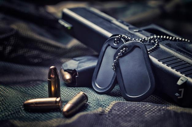 Militaire penningen liggen op een pistool. het concept van het leger, oorlog, politiek conflict.