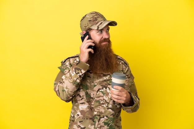 Militaire roodharige man over geïsoleerd op gele achtergrond met koffie om mee te nemen en een mobiel