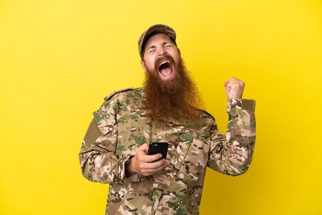 Militaire roodharige man over geïsoleerd op gele achtergrond met telefoon in overwinningspositie