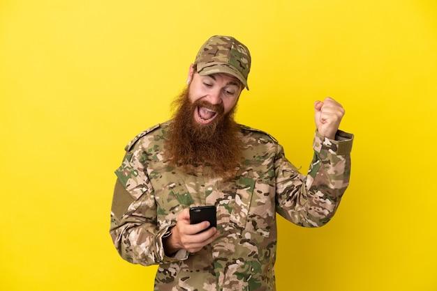 Militaire roodharige man over geïsoleerd op gele achtergrond verrast en het verzenden van een bericht