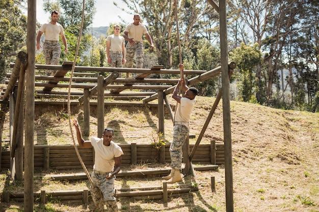 Militaire soldaten die touwklimmen trainen