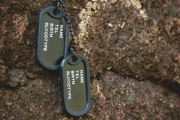 Militaire tag opgehangen op de rots op de rotsachtergrond in het bos. concept van soldatenoffer en wapenstilstand.