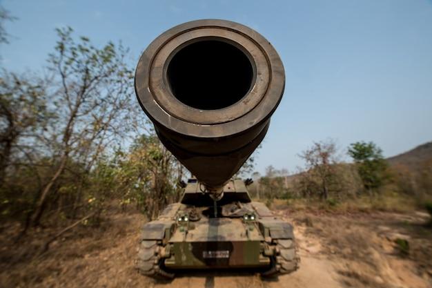 Militaire tank klaar om aan te vallen en over een verlaten slagveldterrein te bewegen