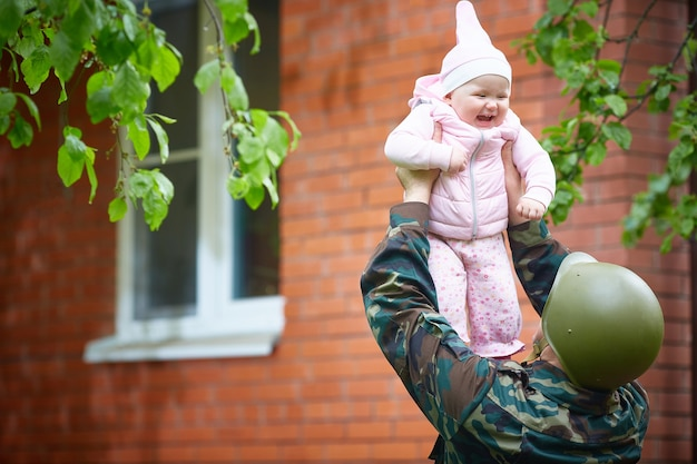 Militaire vader kwam uit de oorlog of de oefeningen en gooit vrolijk de baby