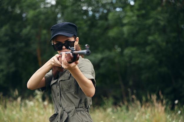 Militaire vrouw houdt een wapen in je handen zonnebril gericht op frisse lucht