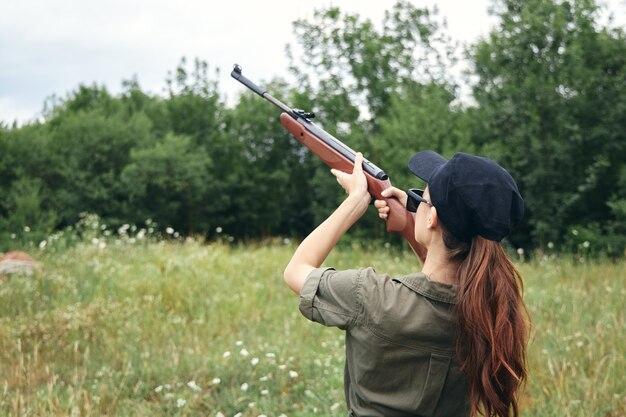 Militaire vrouw met een pistool gericht op jacht op groene bladeren