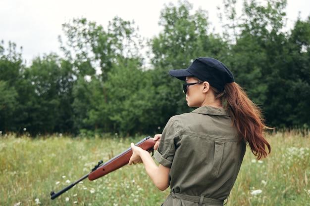 Militaire vrouw met een pistool jacht levensstijl groene bladeren