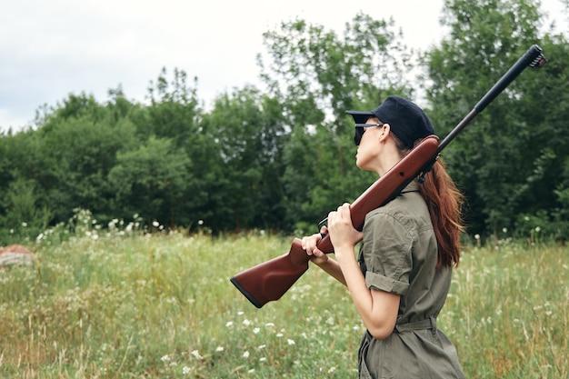 Militaire vrouw shotgun op schouders frisse lucht jacht op groene overall