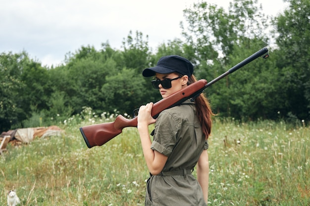 Militaire vrouw verse lucht reizen met een pistool op zijn schouder zwarte pet groen
