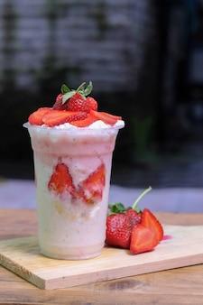 Milkshake met stukjes aardbei, in plastic beker, heerlijk en vers