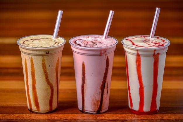 Milkshakes in plastic bekers en rietjes op een donkere houten tafel.