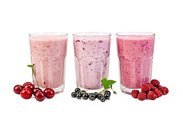 Milkshakes met zwarte bessen, kersen, frambozen in glas geïsoleerd op een witte achtergrond