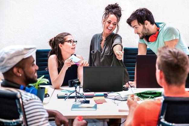 Millenial friends-medewerkers groeperen werknemers op de computer in de opstartstudio
