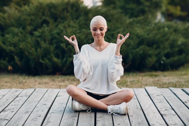 Millenial jonge vrouw blond kort haar buiten doet yoga lotus