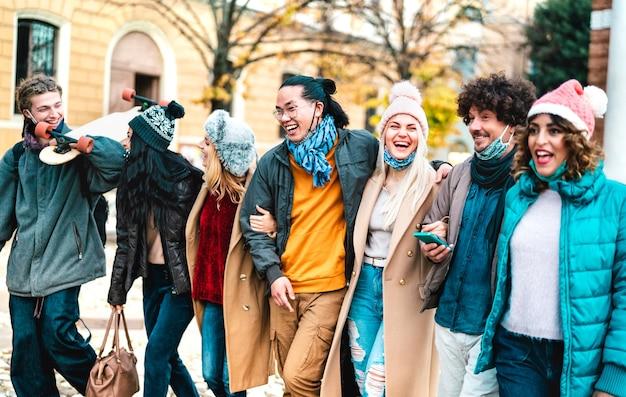 Millenial mensen lopen en hebben samen plezier met het dragen van een open gezichtsmasker in de oude stad