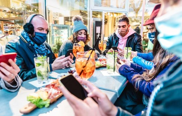 Millenial vrienden met behulp van mobiele smartphones bij cocktailbar