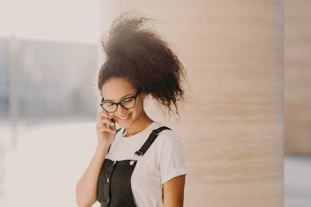 Millennial afro-vrouw spreekt via mobiele telefoon