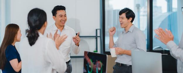 Millennial groep van jonge ondernemers azië zakenman en zakenvrouw vieren het geven van vijf na de deal gelukkig gevoel en ondertekening van contract of overeenkomst in de vergaderzaal in kleine moderne kantoor.