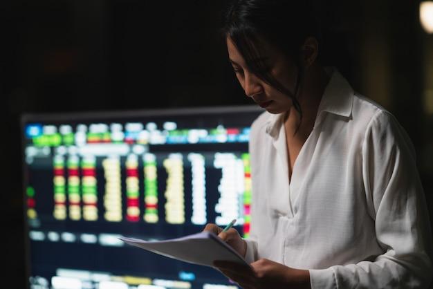 Millennial jonge chinese zakenvrouw werken 's avonds laat stress met project onderzoeksprobleem op laptop in de vergaderzaal op kleine moderne kantoor. azië mensen beroepsgebrek syndroom concept.