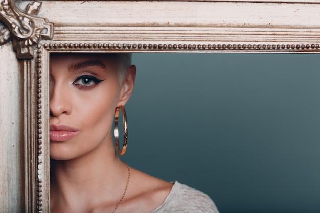 Millennial jonge vrouw met kort blond haar houdt vergulde fotolijst in handen achter haar gezichtsportret.