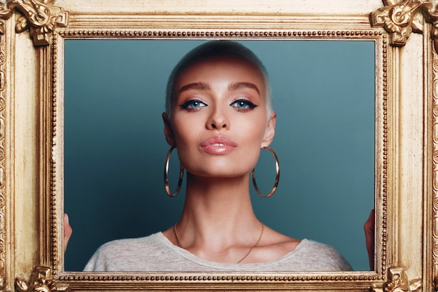 Millennial jonge vrouw met kort blond haar houdt vergulde fotolijst in handen