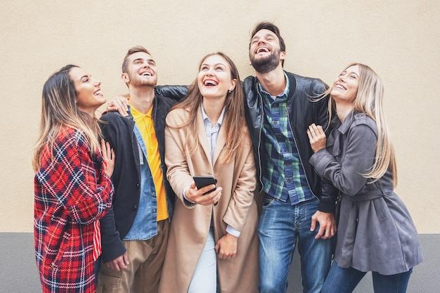 Millennials die bij de muur staan en van elkaar genieten - tieners gebruiken smartphone en glimlachen terwijl ze een selfie proberen te maken - vrienden hebben samen plezier