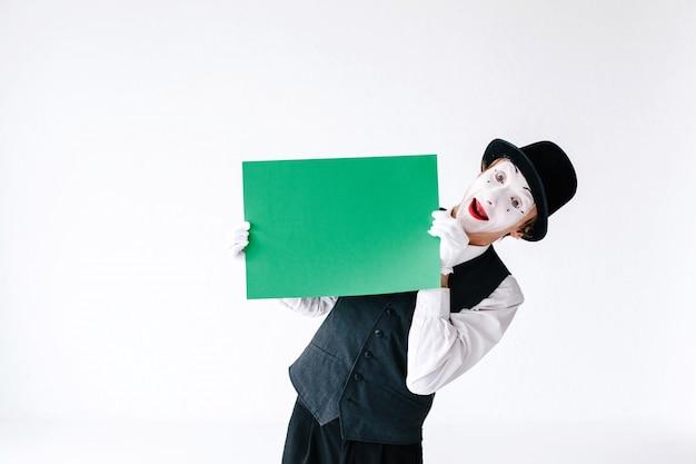 Mime kijkt van achter groen papier in zijn armen