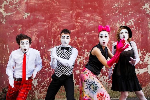 Mimespelers staande op een rode muur
