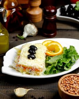 Mimosa-salade gegarneerd met olijven en zijkruiden