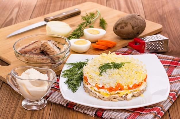 Mimosasalade en ingrediënten voor zijn voorbereiding op de lijst