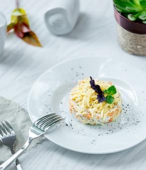 Mimosasalade met gehakte parmezaanse kaas en kruiden.