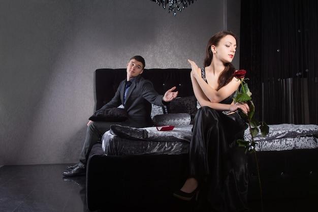 Minachtende aantrekkelijke jonge vrouw zittend op het bed gekleed in elegante zwarte avondkleding en negeert haar echtgenoot of vriend terwijl hij haar smeekt hem te vergeven of een indiscretie over het hoofd te zien