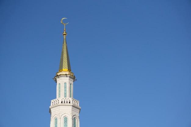 Minaret van een moslim moskee over blauwe hemel. islamitische en islamitische architectuur