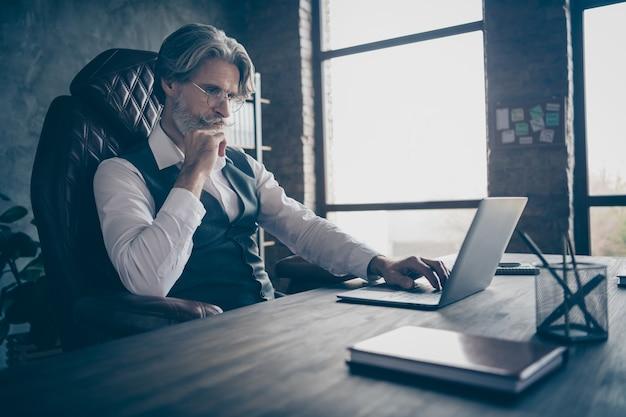 Minded intelligente oude zakenman werken op laptop denken in kantoor