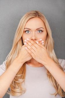 Minder informatie. verraste jonge blonde haarvrouw die haar mond bedekt en naar de camera staart