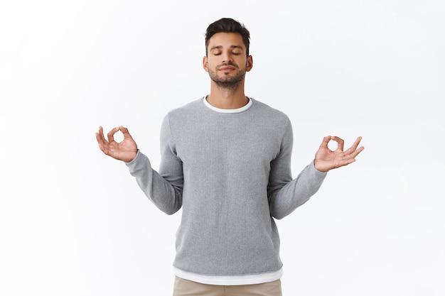 Mindful geduldige en ontspannen jonge gelukkige man, oefen ademhalingsoefeningen, houd handen zijwaarts en lach opgelucht, laat stress los tijdens werktijd neem pauze om te mediteren, witte muur