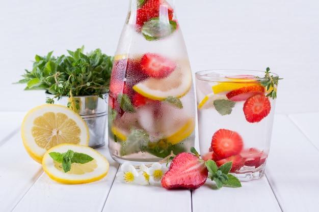 Mineraal doordrenkt water met aardbei, ijs, kruiden en muntblaadjes op wit oppervlak, zelfgemaakte detox soda water recept.