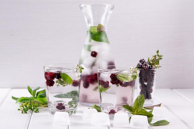 Mineraal doordrenkt water met bramen, ijs, kruiden en muntblaadjes op een wit oppervlak, zelfgemaakte detox soda water recept.