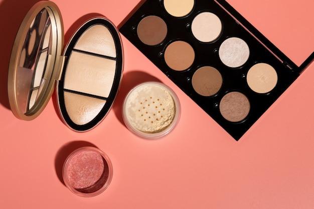 Mineraal poeder, geperste blush en kit voor gezichtscontouren op een roze achtergrond. close-up shot